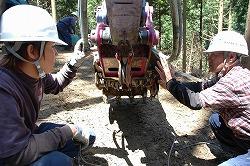 この機械は集材ではスイングヤーダのアームとなり、作業路開設時にヘッドのグラップル付きバケットが威力を発揮。斎藤久義さん(右)が若い社員を現場で指導する